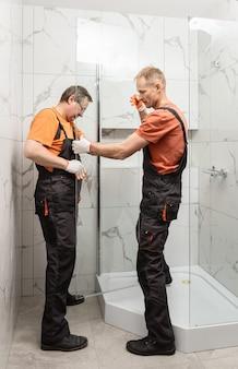 労働者はガラスの壁のシャワーエンクロージャーを設置しています。
