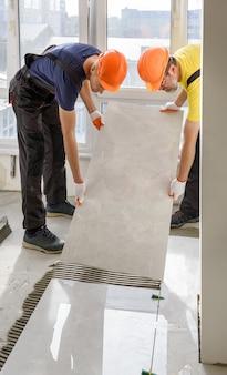 Рабочие устанавливают на пол большую керамическую плитку