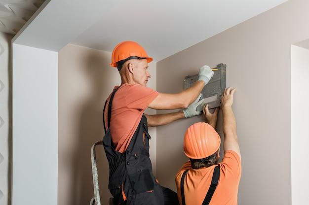 Рабочие устанавливают сплит-систему домашнего кондиционера.
