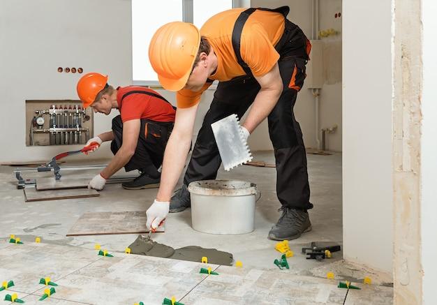 労働者は床にセラミックタイルを設置しています