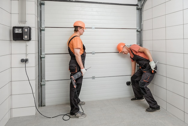 The workers are installing lift gates in the garage.