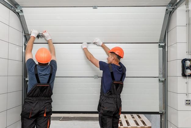 Рабочие устанавливают подъемные ворота гаража.