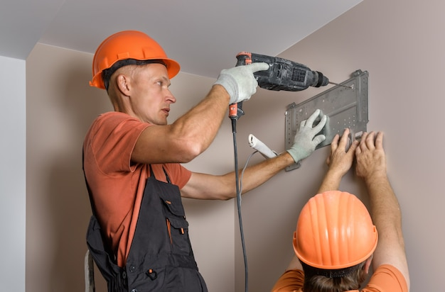 Workers are installing a split system for a home air conditioning system.
