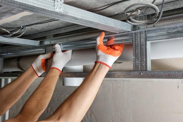 Рабочие монтируют сложный каркас под гипсокартон на потолок
