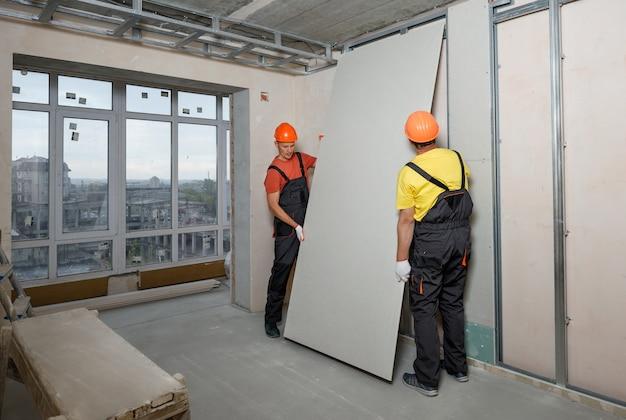 Рабочие монтируют гипсокартон к стене