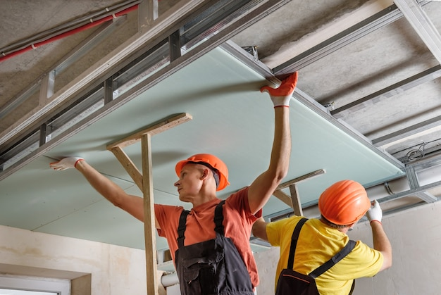 Workers are mounting plasterboard to the ceiling