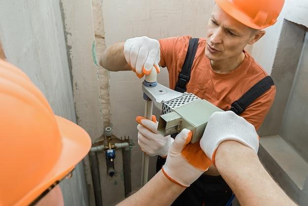 Рабочие паяют настенные трубы для встроенного душа.