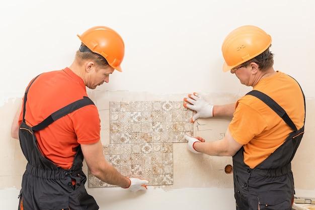 労働者は壁のセラミックタイルを試しています