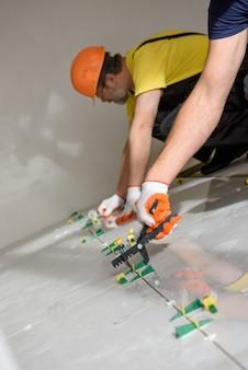 労働者は、プラスチック製のクランプとウェッジを使用して、床の大きなセラミックタイルを平らにします。