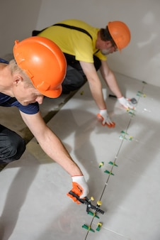 Workers are using plastic clamps and wedges to level the large ceramic tile on the floor