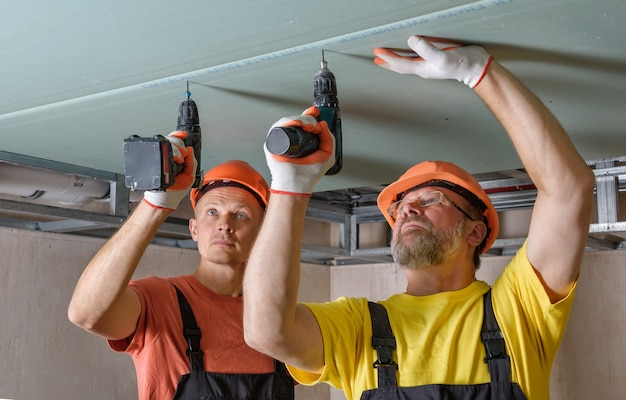 Workers are using screwdrivers to attach plasterboard to the ceiling