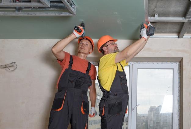 Рабочие с помощью отверток прикрепляют гипсокартон к потолку.