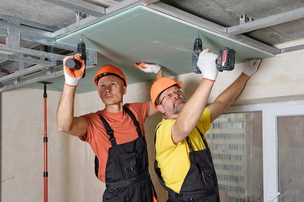 Рабочие используют отвертки для крепления гипсокартона к потолку