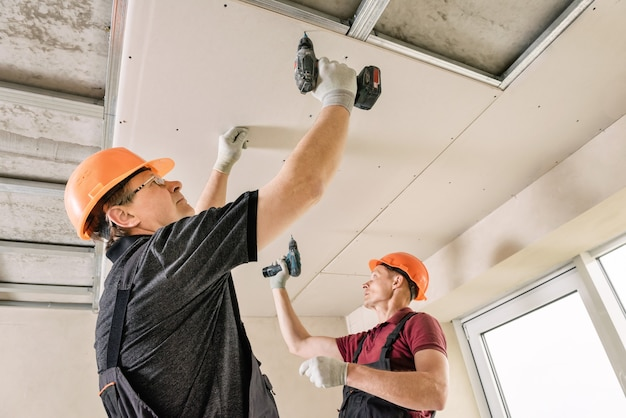 Рабочие с помощью шурупов и отвертки прикрепляют гипсокартон к потолку.