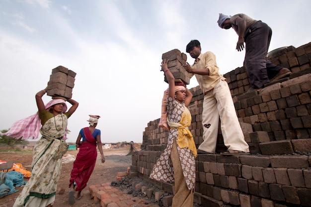 労働者はレンガの窯で加熱するためにスタックに生のレンガを配置します