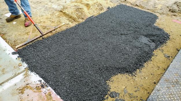 Workers on asphalting paver road street repairing works