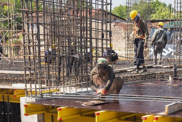 建設現場の作業員は、基礎をコンクリートで埋めるために溶接作業を行います