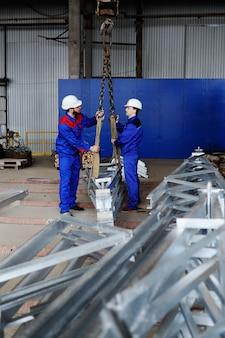 Рабочие на заводе грузят груз на крюк крана на фоне производства