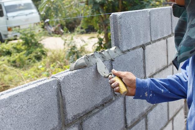 Рабочие строят стену