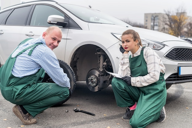 Workers at car service station examining tyre
