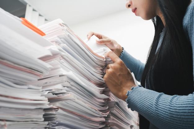 オフィスの机の上の紙の山の文書をチェックする労働者