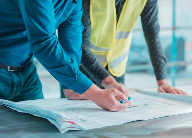 Рабочие проверяют архитектурный план проекта.