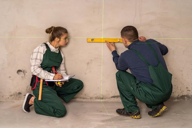 レーザーレベルツールで壁をチェックする労働者