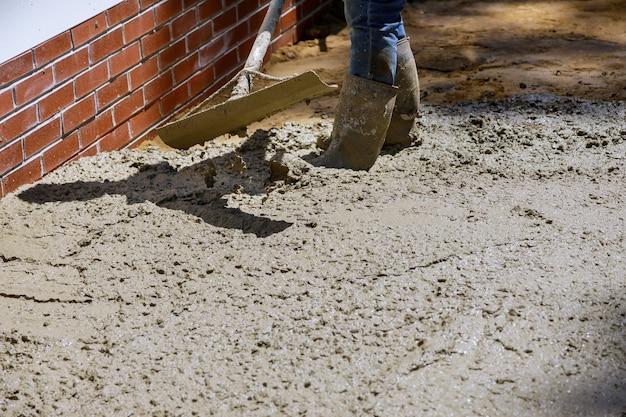 보도에 주거하는 동안 시멘트를 붓는 노동자 콘크리트 믹서