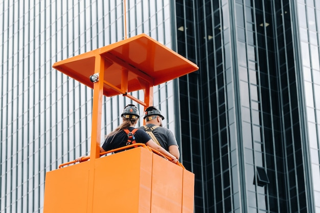 Workers in a construction cradle climb on a crane to a large glass building.the crane lifts the workers in the car seat.construction.