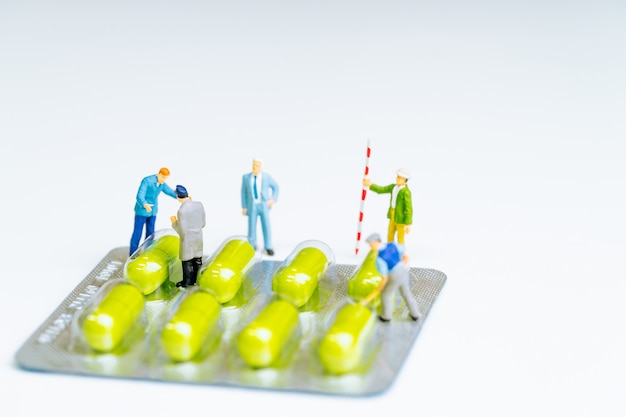 Workers digging medicine pills in white background