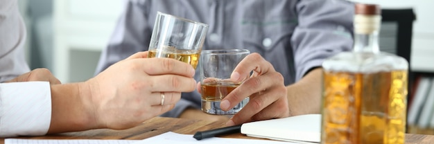 Workers drinking whiskey in office