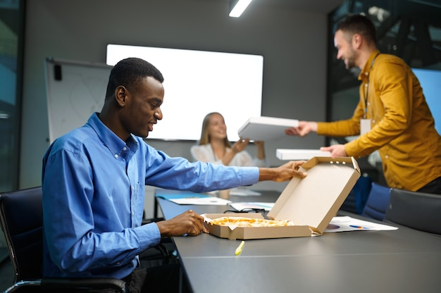 Workers eats pizza, business lunch in it office