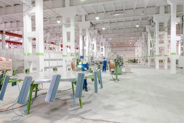 ラジエーターへの銅パイプの溶接とはんだ付けに従事するワークショップの労働者工場