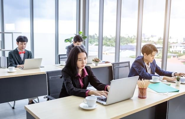 다양한 성별(lgbt)을 가진 아시아 사업가 그룹이 사무실 회의실의 공동 작업 공간에서 일상적인 작업을 수행하는 컴퓨터 작업 책상에 앉아 있습니다.