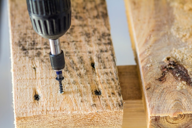 Workers hand with electric screwdriver screwing a screw into wooden board