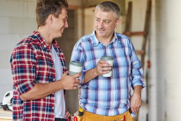 Lavoratori che hanno una piccola chiacchierata mentre bevono una tazza di caffè