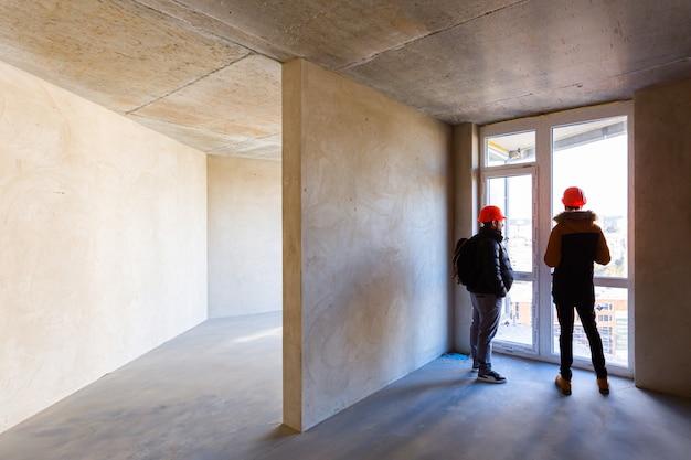 Рабочие в касках, проверяют ход конструкции, на стройплощадке большой небоскреб