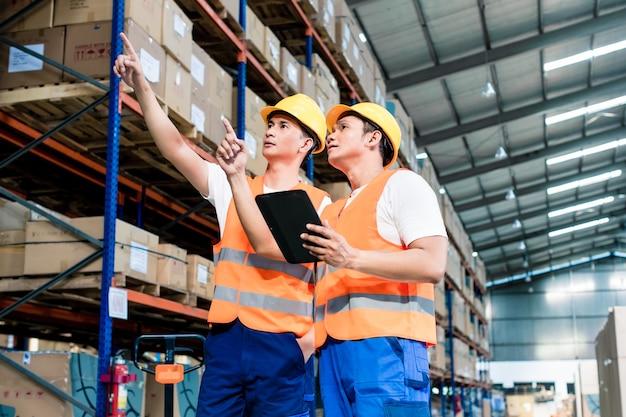 Рабочие на складе логистики в списке проверки вилочного погрузчика