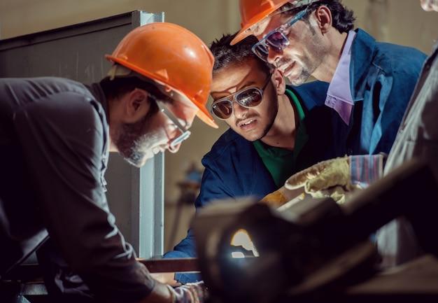 Workers in industrial factory welding