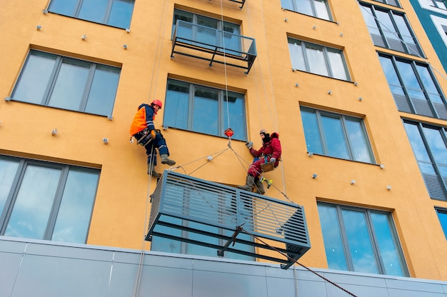 Workers install niches for air conditioners on the house under construction