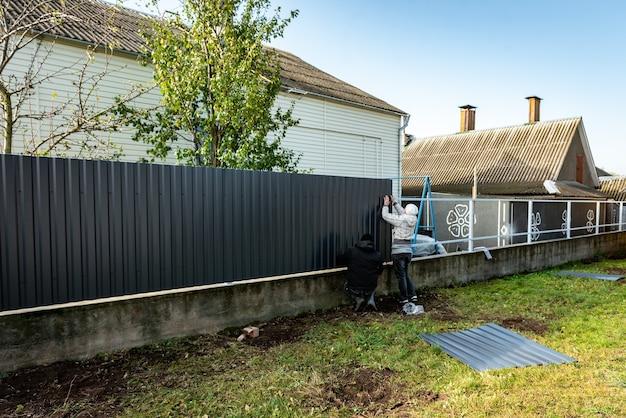 작업자는 금속 프로필에서 회색 울타리를 설치합니다.