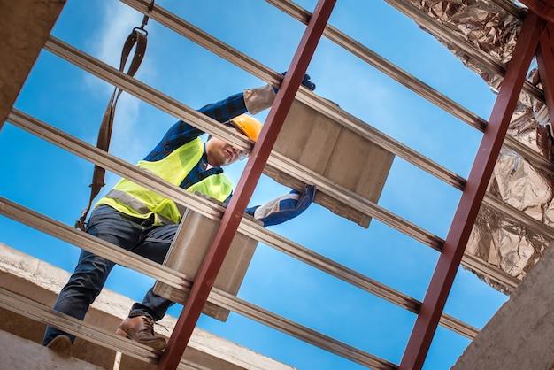 Рабочие, монтирующие крыши в защитной одежде. строительство крыши дома, производство керамической черепицы или черепицы cpac.