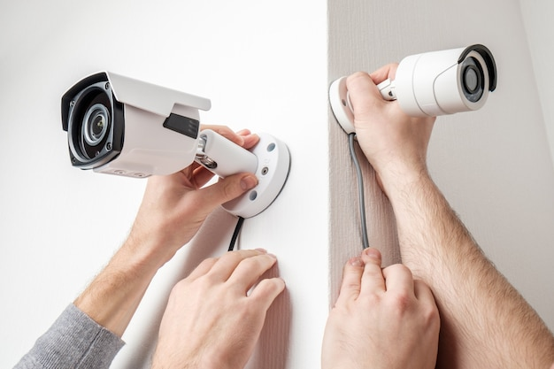 Workers installing video surveillance cameras on walls