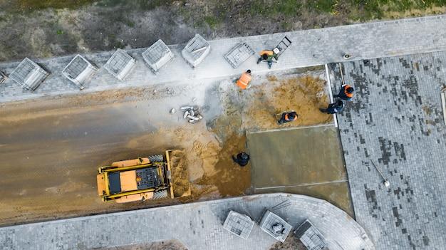 Рабочие укладывают тротуарную плитку сверху на вид из дрона