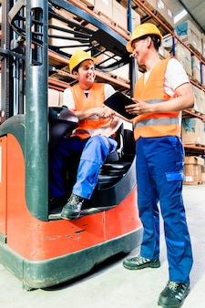Workers in logistics warehouse at forklift checking list