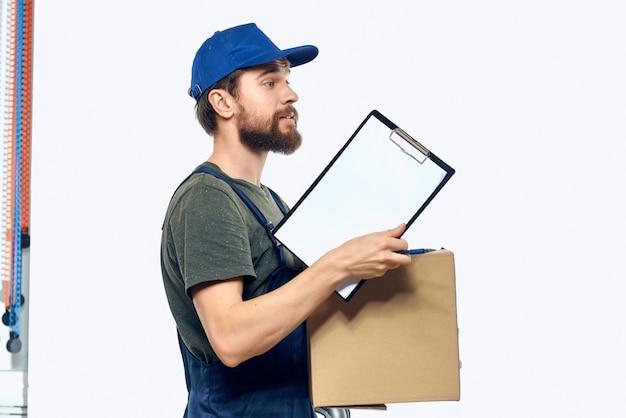 青い帽子をかぶった労働者の男は、配達の専門家を梱包する彼の手に箱を持っています。高品質の写真