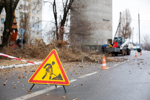 Workers in the municipal utilities cut branches from trees, blocking the street
