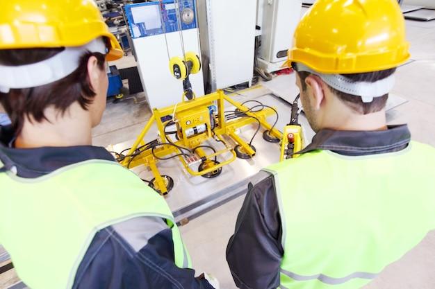 Рабочие возле подъемного устройства для листового металла на заводе