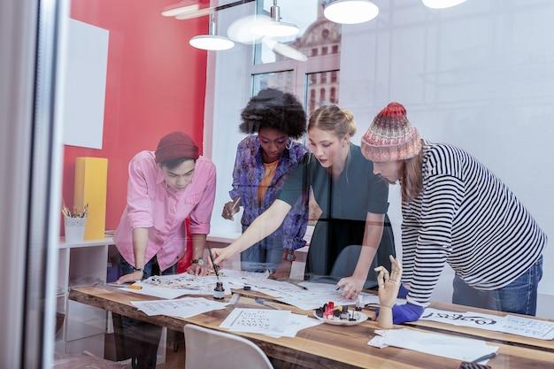 雑誌の労働者。新しいプロジェクトに取り組んでいるファッション雑誌の4人の才能のあるクリエイティブワーカー