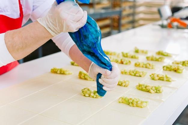 製菓工場の労働者は、中身の入ったデザートを準備します